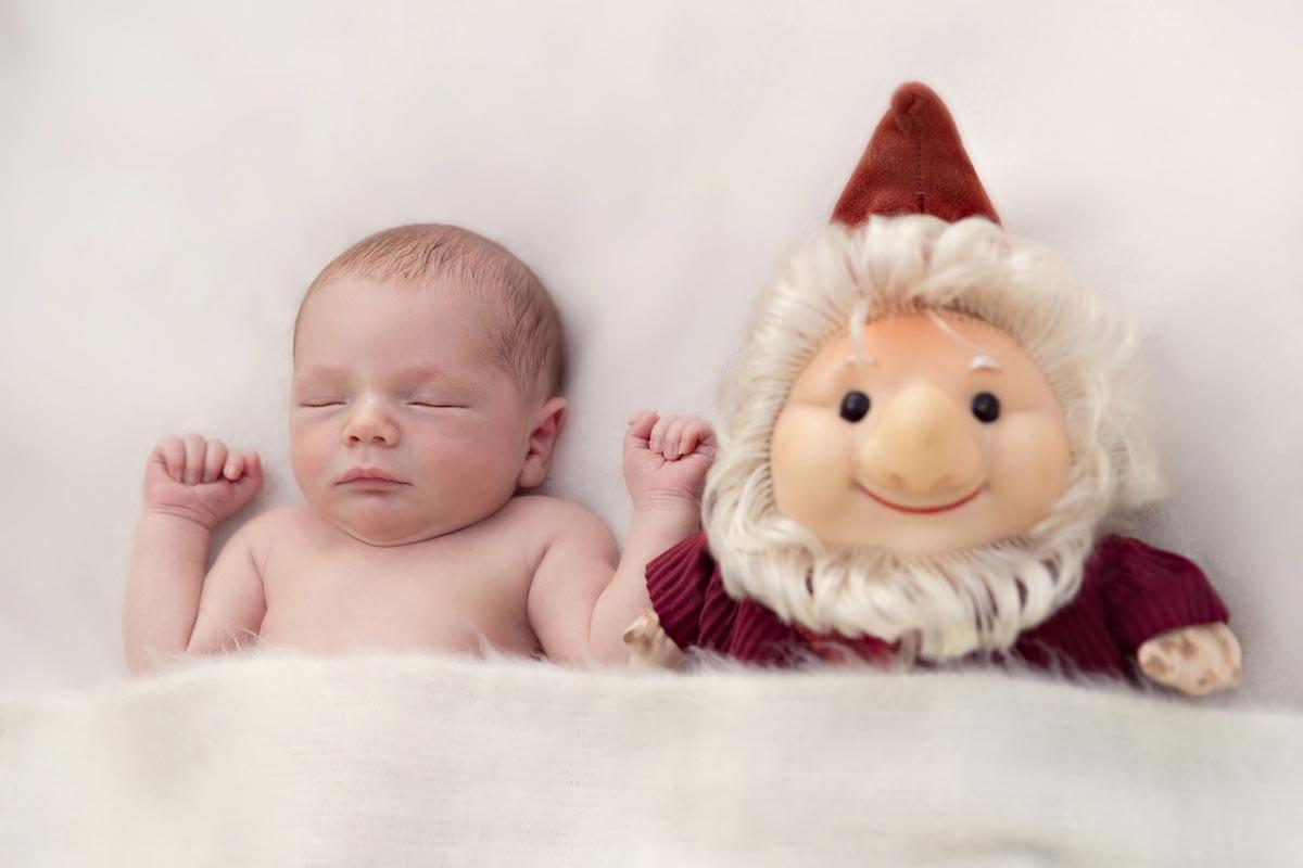 Neugeborenes Baby schlaeft neben eine Marionette waehrend des Neugeborenen Fotoshooting
