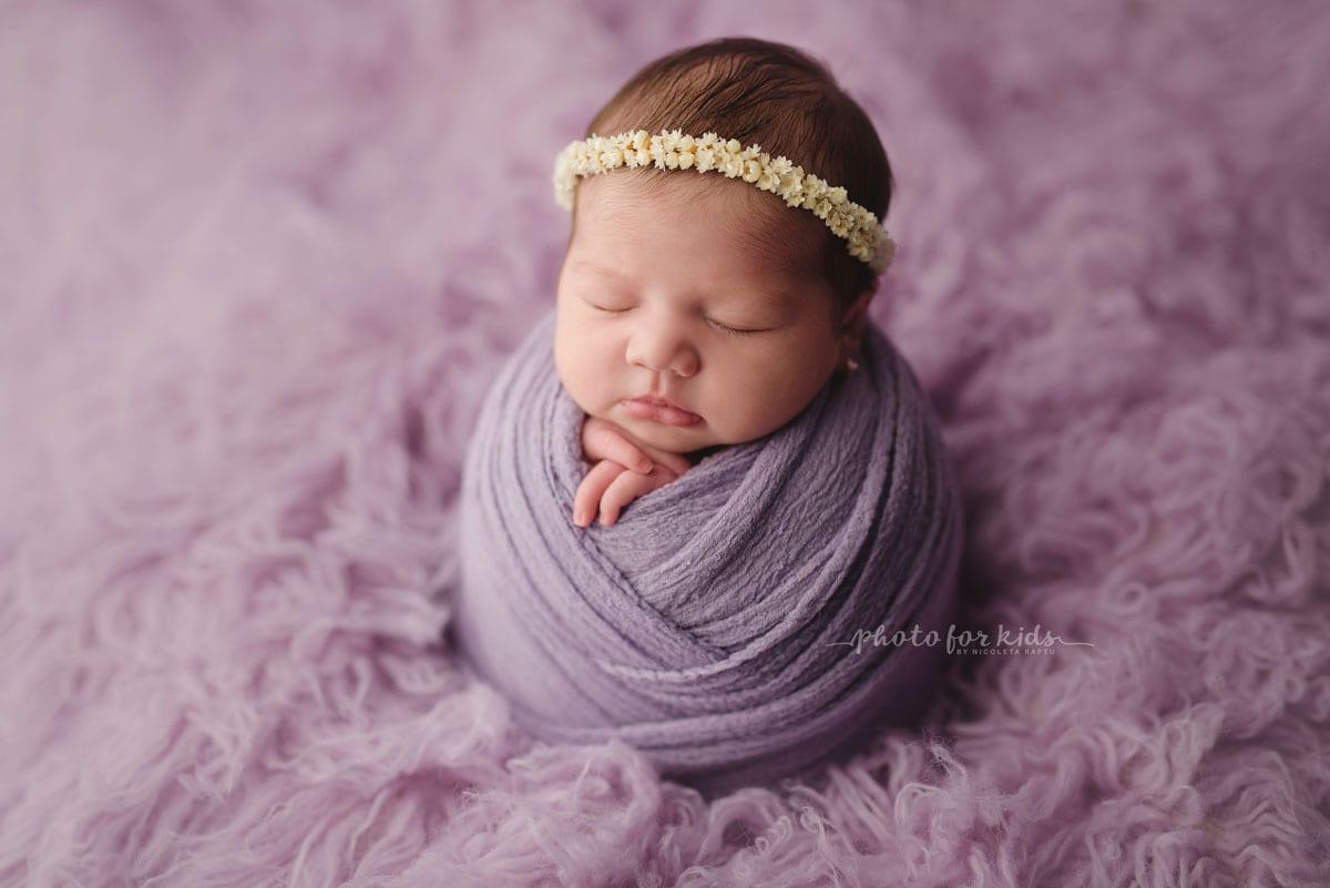 Neugeborenes Maedchen im lila Outfit schlaeft in einem Fotoshooting von Nicoleta Raftu