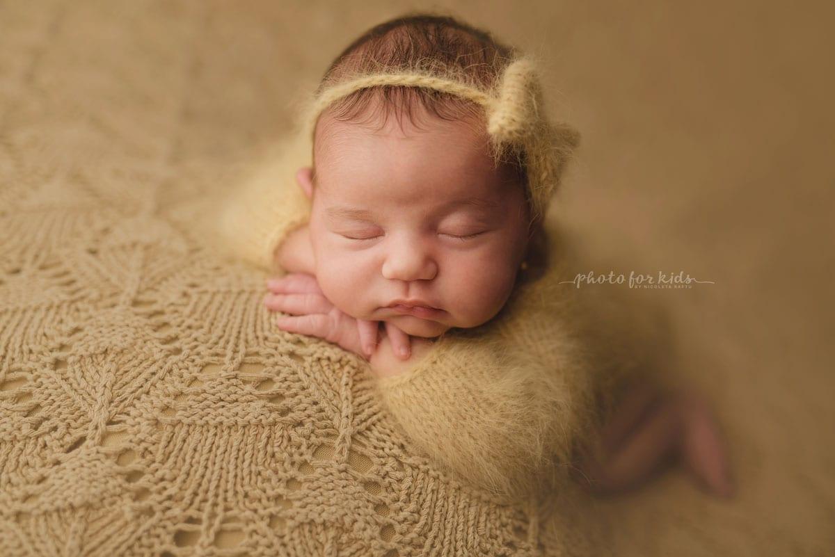 Neugeborenes Maedchen im orangefarbenen Outfit schlaeft auf dem Bauch waehrend eines Fotoshootings in Nicoleta Raftu Fotostudio