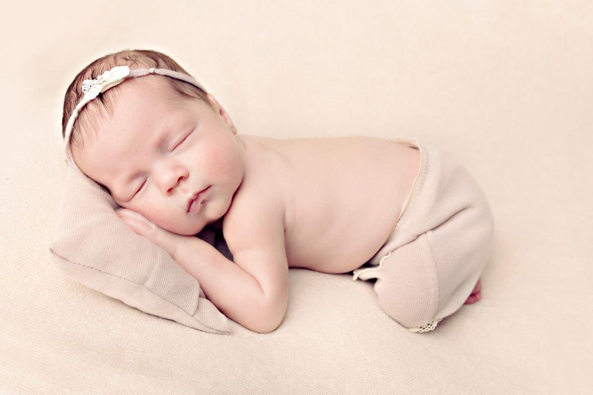 Neugeborenes Maedchen mit weissem Diadem schlaeft mit Kopf auf einem kleinen Kissen waehrend der neugeborenen Fotosession in Muenchen