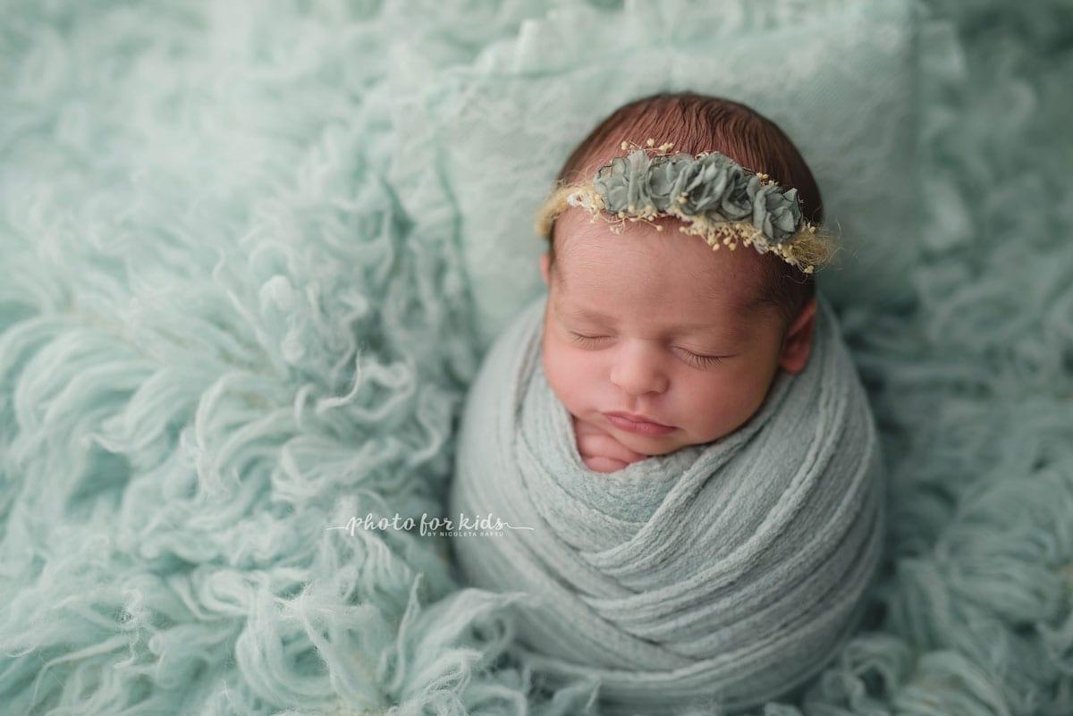 Neugeborenes im gruenen Outfit schlaeft waehrend eines Fotoshootings im Fotostudio von Nicoleta Raftu