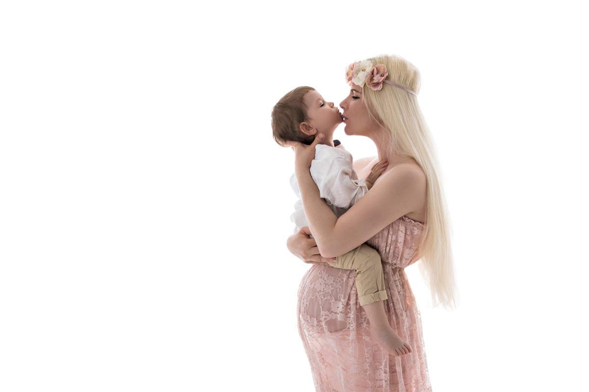 Schwangere Frau im rosafarbenen Kleid haelt ein Kind und posiert waehrend eines Babybauch Fotoshootings im Carmen Bergmann Studio in Muenchen