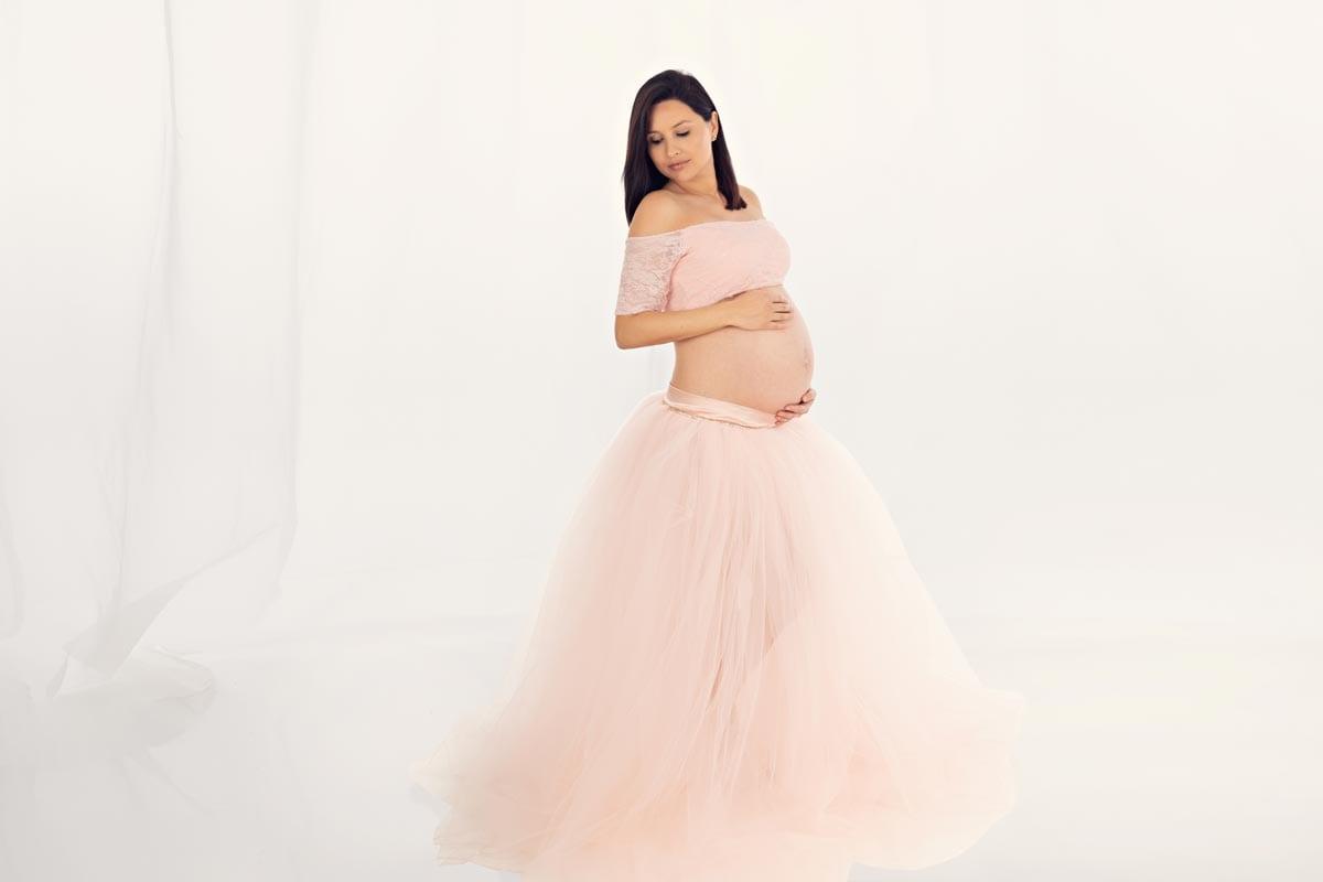 Schwangere Frau im rosafarbenen Kleid und mit dunklem Haar schaut ueber die Schulter und posiert waehrend eines Babybauch Fotoshootings in Carmen Bergmanns Fotostudio in Munchen