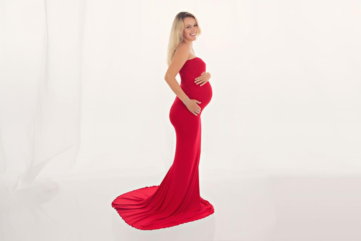 Schwangere Frau mit blonden Haaren und im roten langen Kleid posiert in einem Babybauch Fotoshooting im Carmen Bergmann Fotostudio in Muenchen