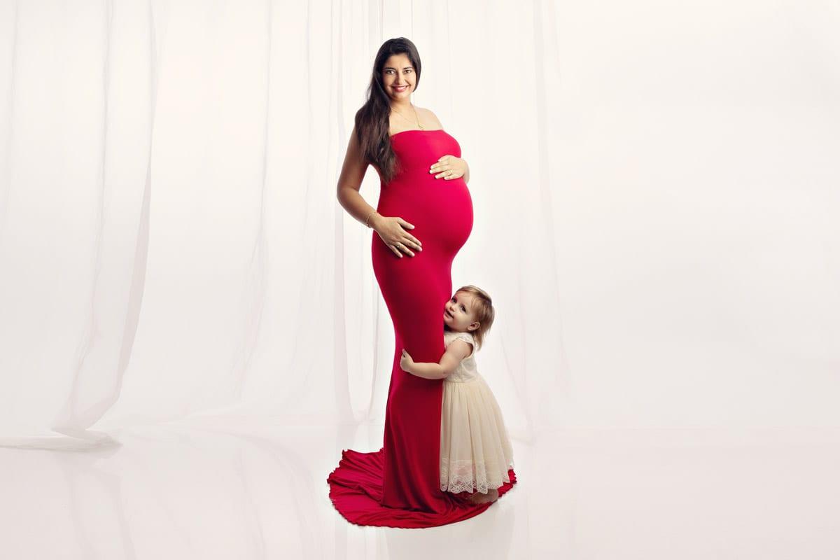 Schwangere Frau mit dunklen Haaren und im roten langen Kleid posiert mit einem Kind waehrend eines Babybauch Fotoshootings im Fotostudio Carmen Bergmann