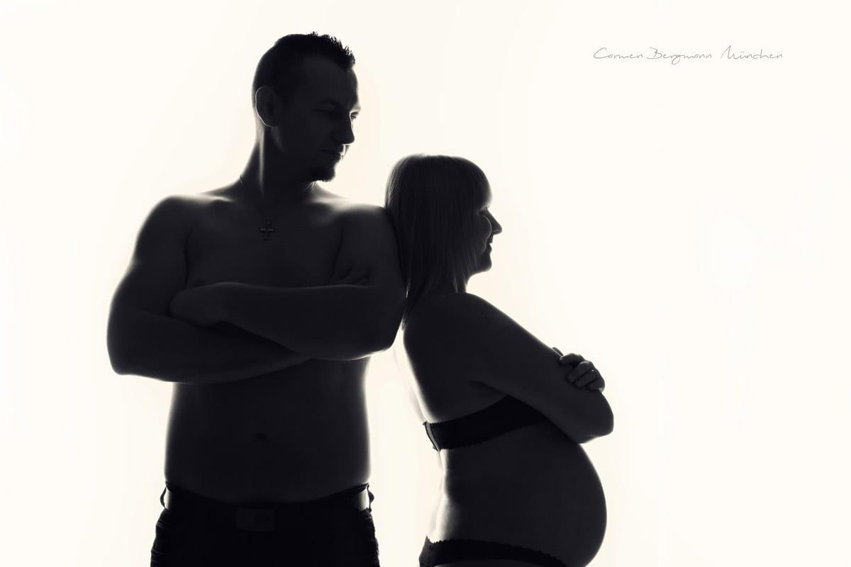 Schwangere Frau mit ihrem Mann posieren auf weissem Hintergrund in einem Schwangerschaft Fotoshooting in Carmen Bergmann Fotostudio in Muenchen