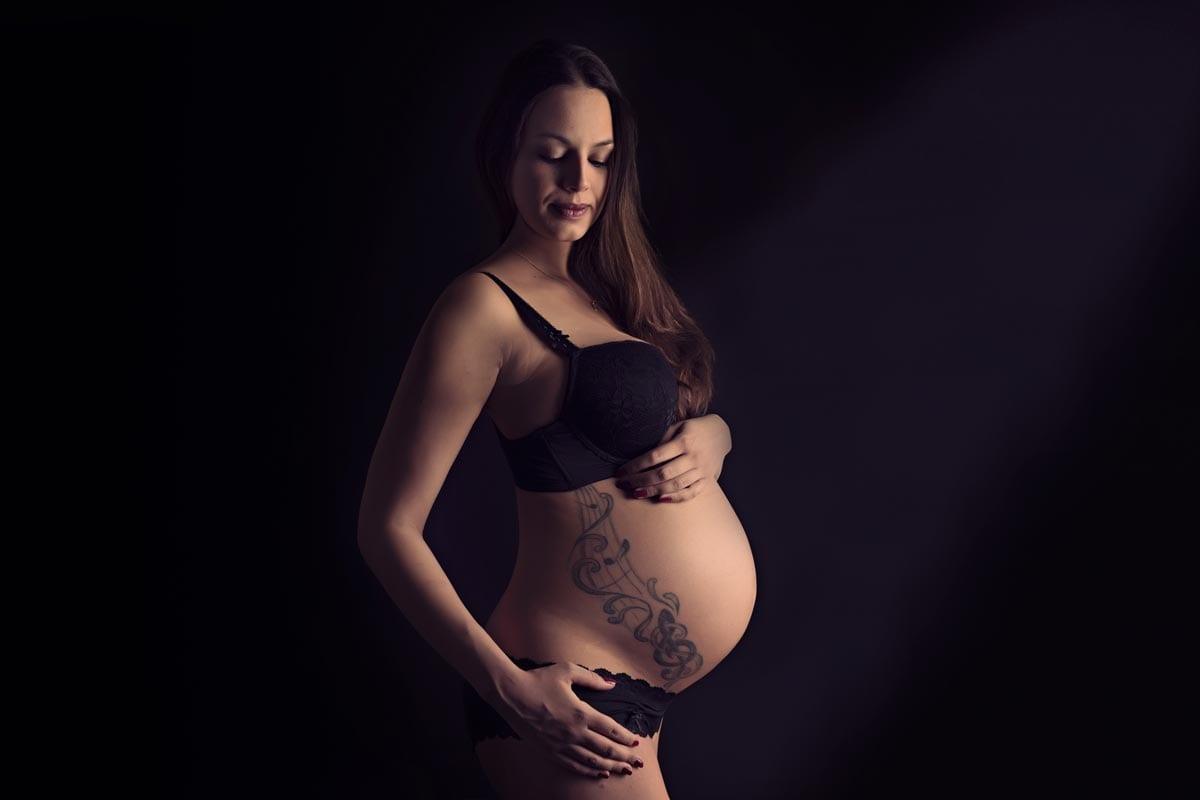 Schwangere Frau mit riesiger Taetowierung auf ihrem Babybauch posiert bei Licht und Schatten waehrend einer Schwangerschaft Fotoshooting im Carmen Bergmann Fotostudio in Muenchen