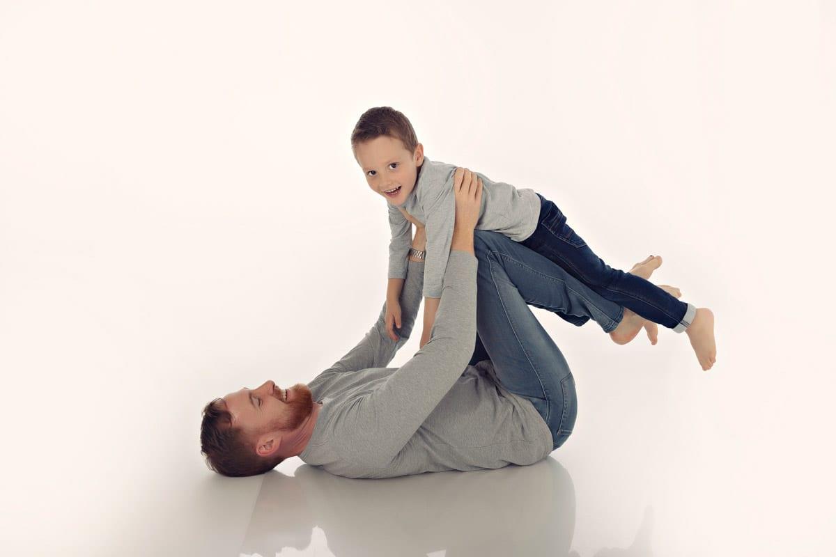 Vater haelt Sohn bei einem Familienfotoshooting im Bergmann Fotostudio in Muenchen auf den Knien