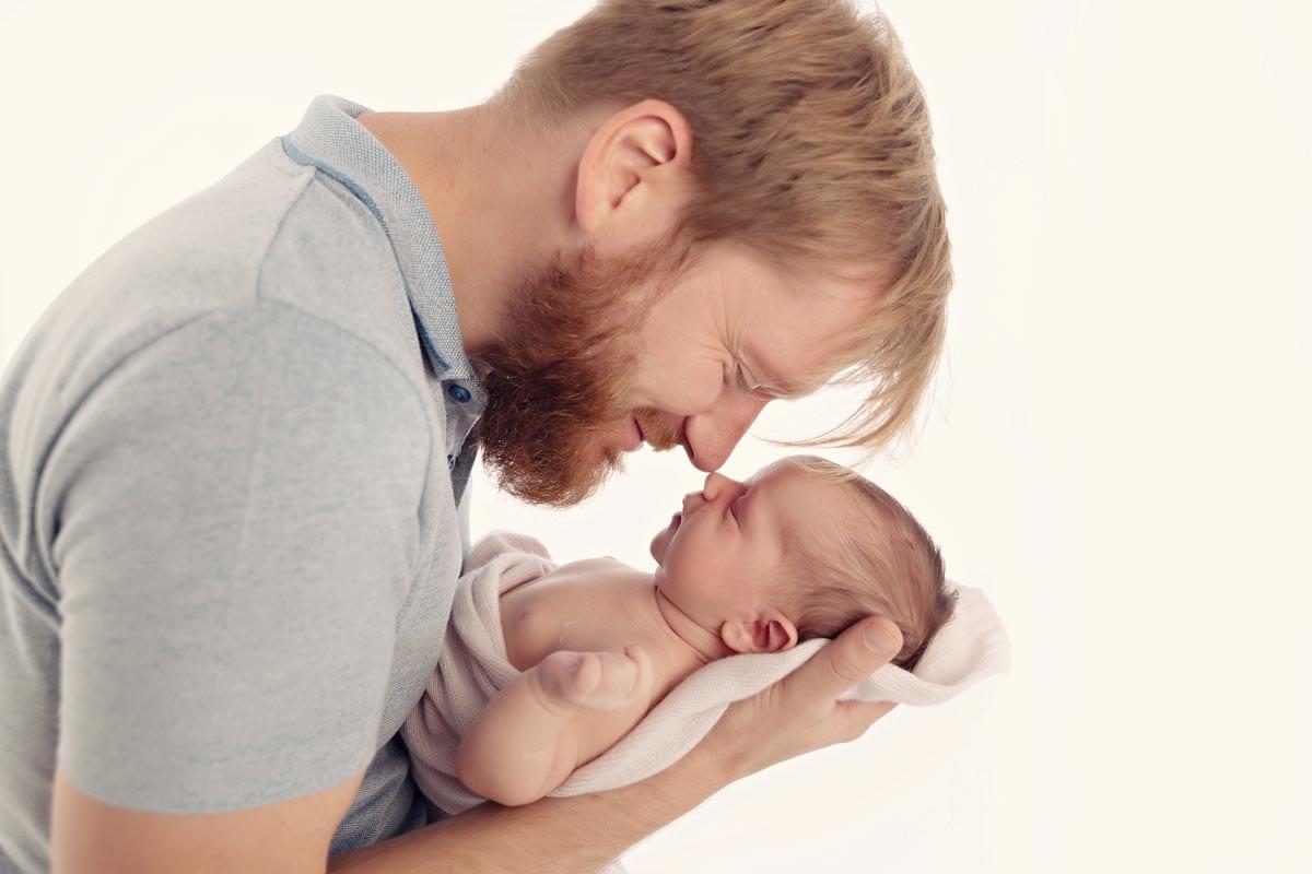 Vater haelt neugeborenes Baby in den Armen und beruehrt Nasen beim neugeborenen Fotoshooting im Carmen Bergmann Photo Studio in Muenchen