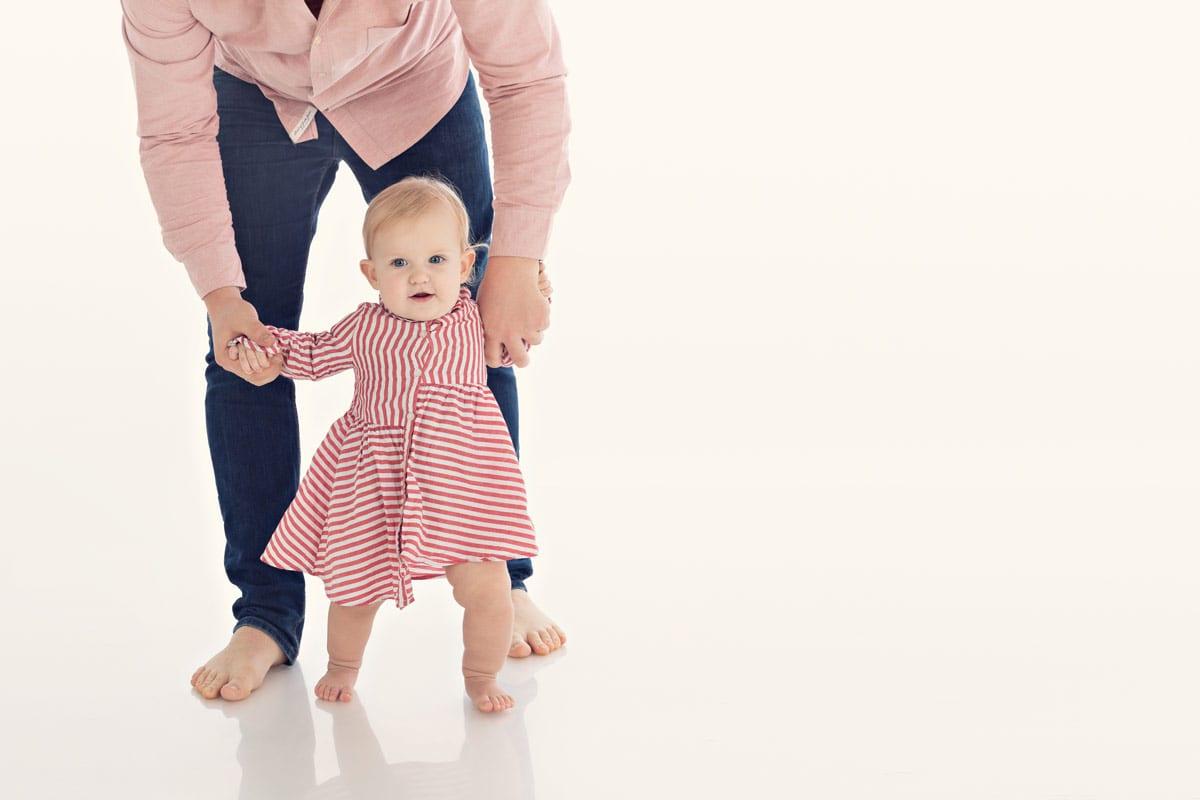 Vater hilft kleinen Maedchen bei den ersten Schritten waehrend eines Fotoshootings im Carmen Bergmann Fotostudio in Muenchen
