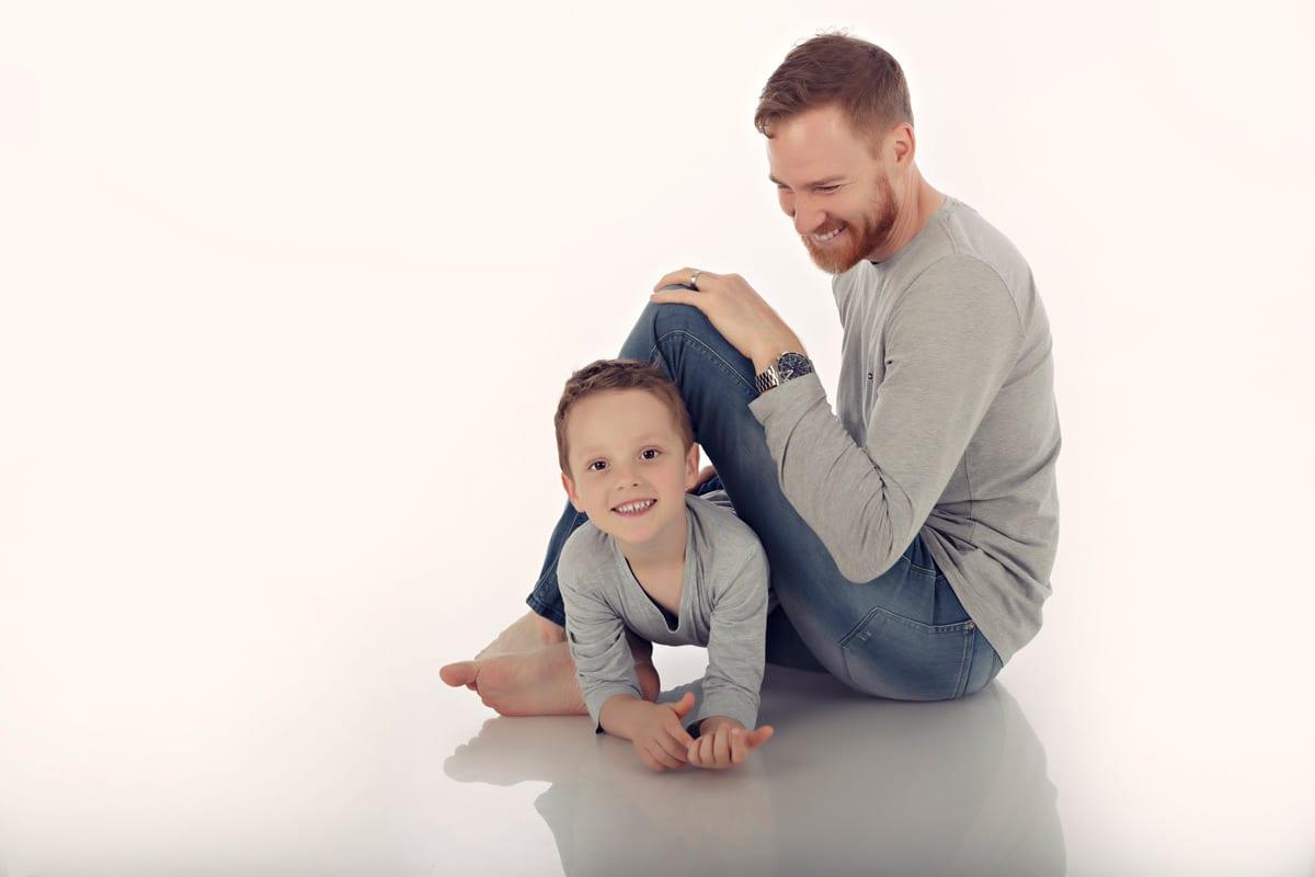 Vater und Sohn sitzen im Carmen Bergmann Photo Studio waehrend eines Familienfotoshooting