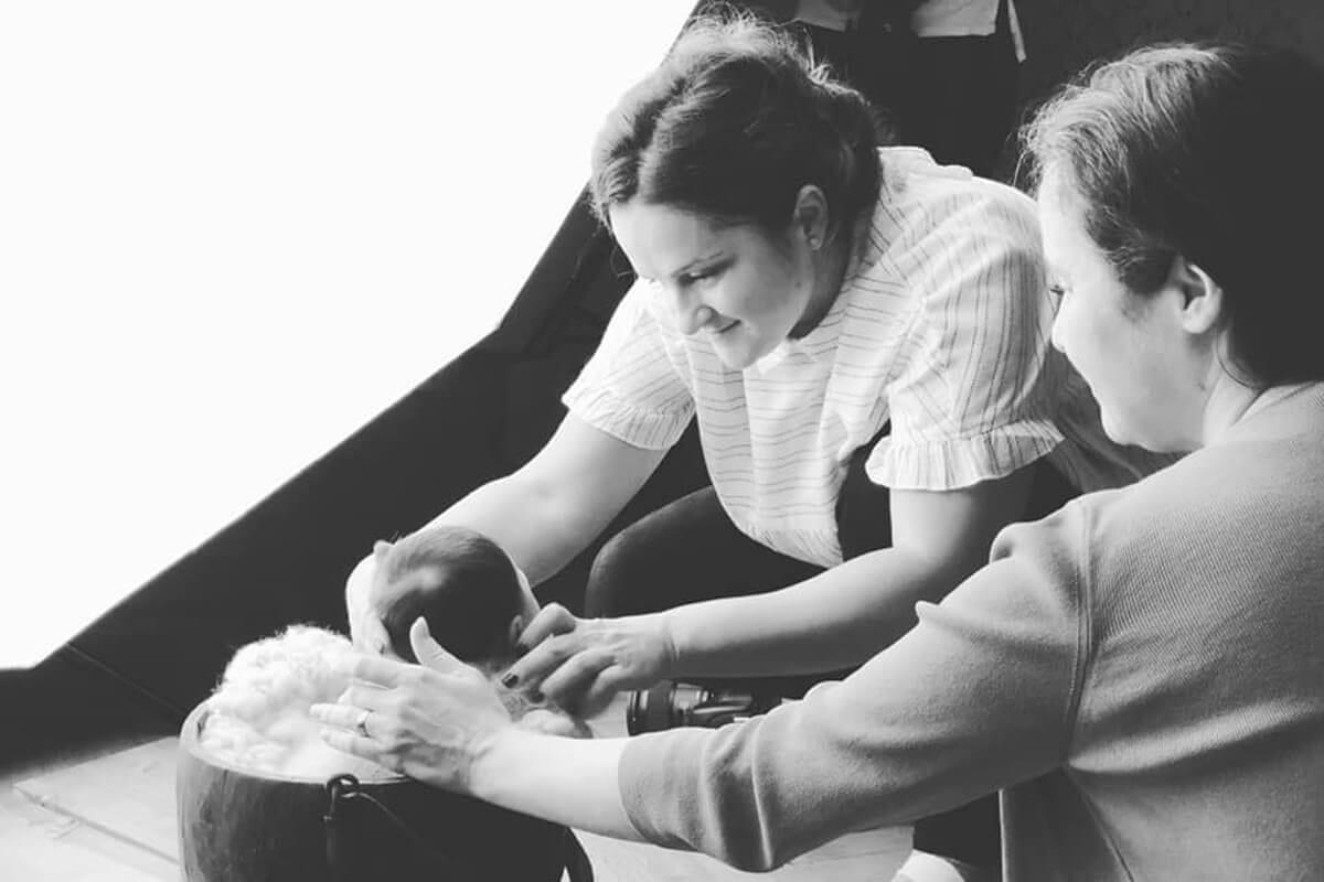 Zwei Fotografen bereiten ein Baby fuer ein Fotoshooting waehrend eines Babyfotografie-Workshops vor