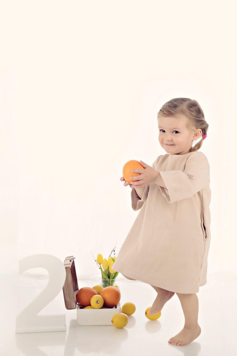 Zwei Jahre altes Maedchen spielt mit einer Orange und schaut in die Kamera waehrend eines Baby-Fotoshootings