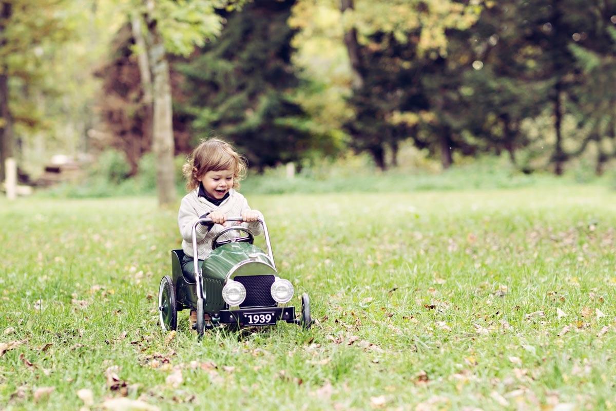 kleiner Junge faehrt ein Spielzeugauto waehrend eines Fotoshootings im Freien Carmen Bergmann