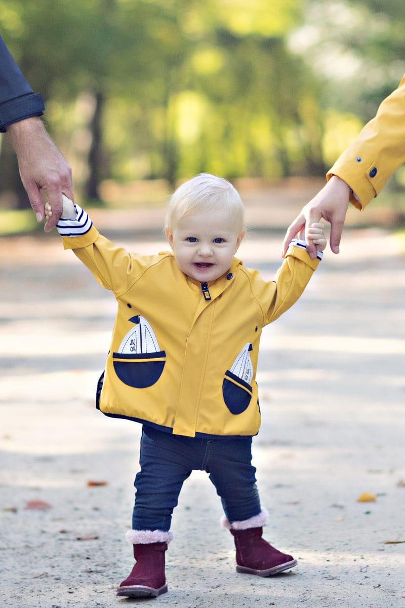 kleines Baby geht mit Eltern auf einer Strasse im Wald waehrend eines Fotoshootings von Carmen Bergmann im Freien