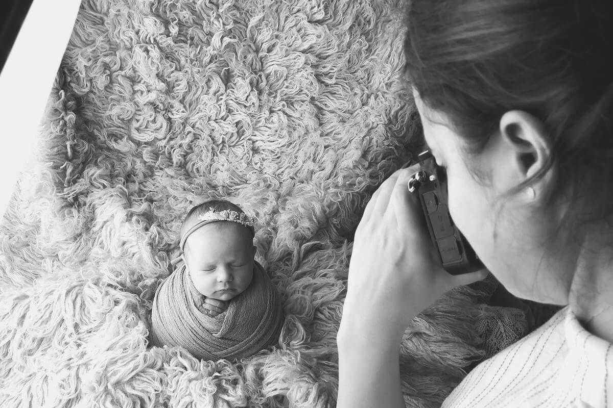 kleines Baby posiert auf einem Bett und wird von einem Fotografen fotografiert