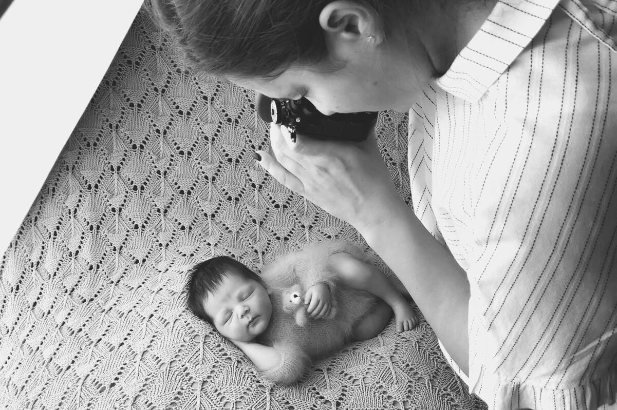 kleines Baby schlaeft auf einem Bett und wird von einem Fotografen fotografiert