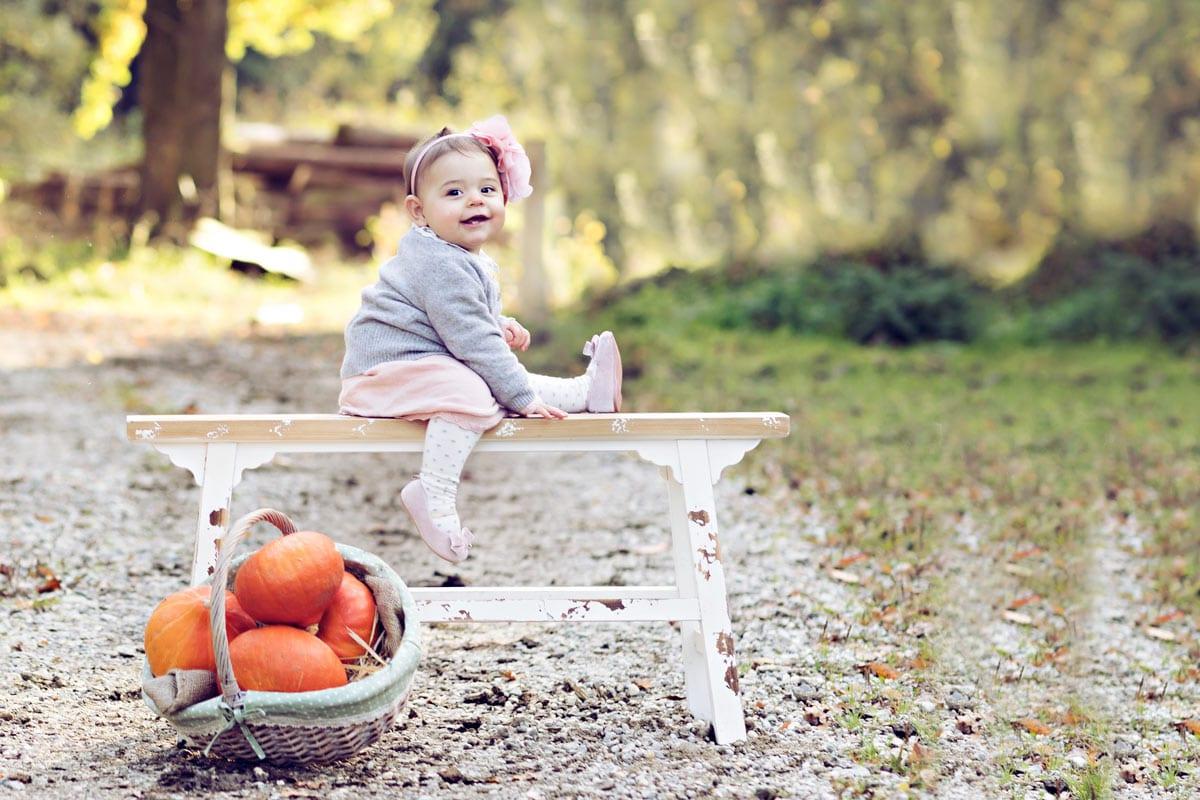 kleines Maedchen sitzt auf einem Bank in der Naehe von orange Kuerbis waehrend eines Fotoshootings im Freien