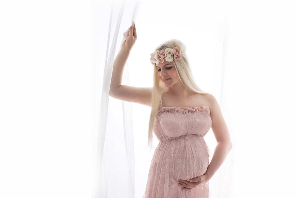 schoene blonde schwangere Frau posiert im rosafarbenen Kleid in Carmen Bergmann Fotostudio waehrend eines Babybauch-Fotoshooting