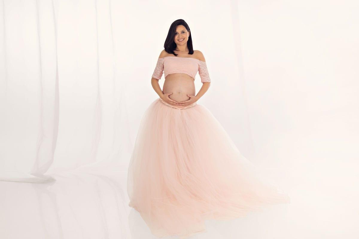 schwangere Dame im rosafarbenen Kleid zeigt ihren Babybauch waehrend eines Babybauch Fotoshootings im Fotostudio Carmen Bergmann in Haidhausen