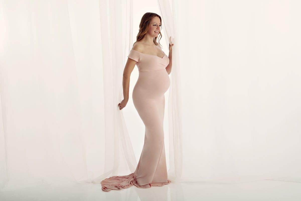 schwangere blonde Frau steht neben einem Vorhang und posiert im rosafarbenen Kleid im Fotostudio von Carmen Bergmann waehrend eines Babybauch Fotoshootings