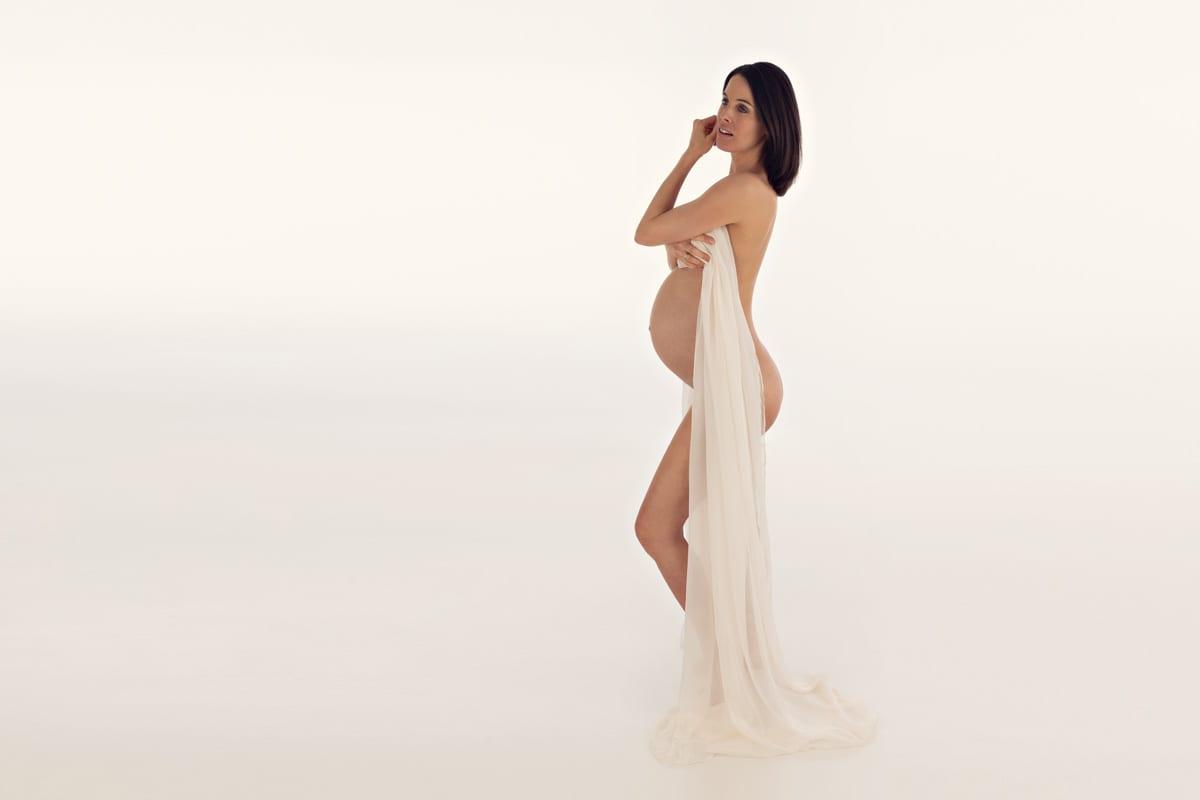 Schwangere posiert mit weissem Kleid waehrend der Fotoshooting im Carmen Bergmann Studio in der Rosenheimer Str. Muenchen