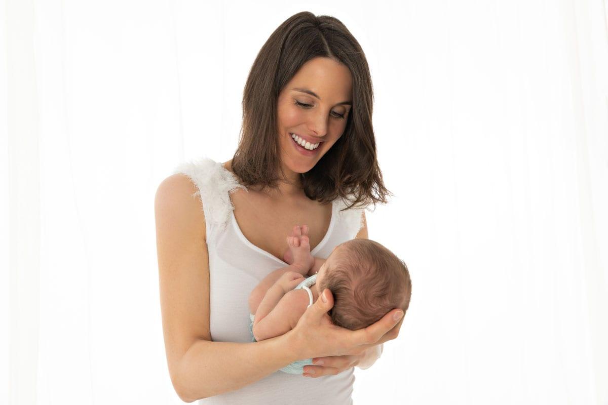Mutter haelt ihr Baby und schaut es beim Neugeborenen beim Fotoshooting im Carmen Bergmann Studio in der Rosenheimer Strasse in Muenchen an