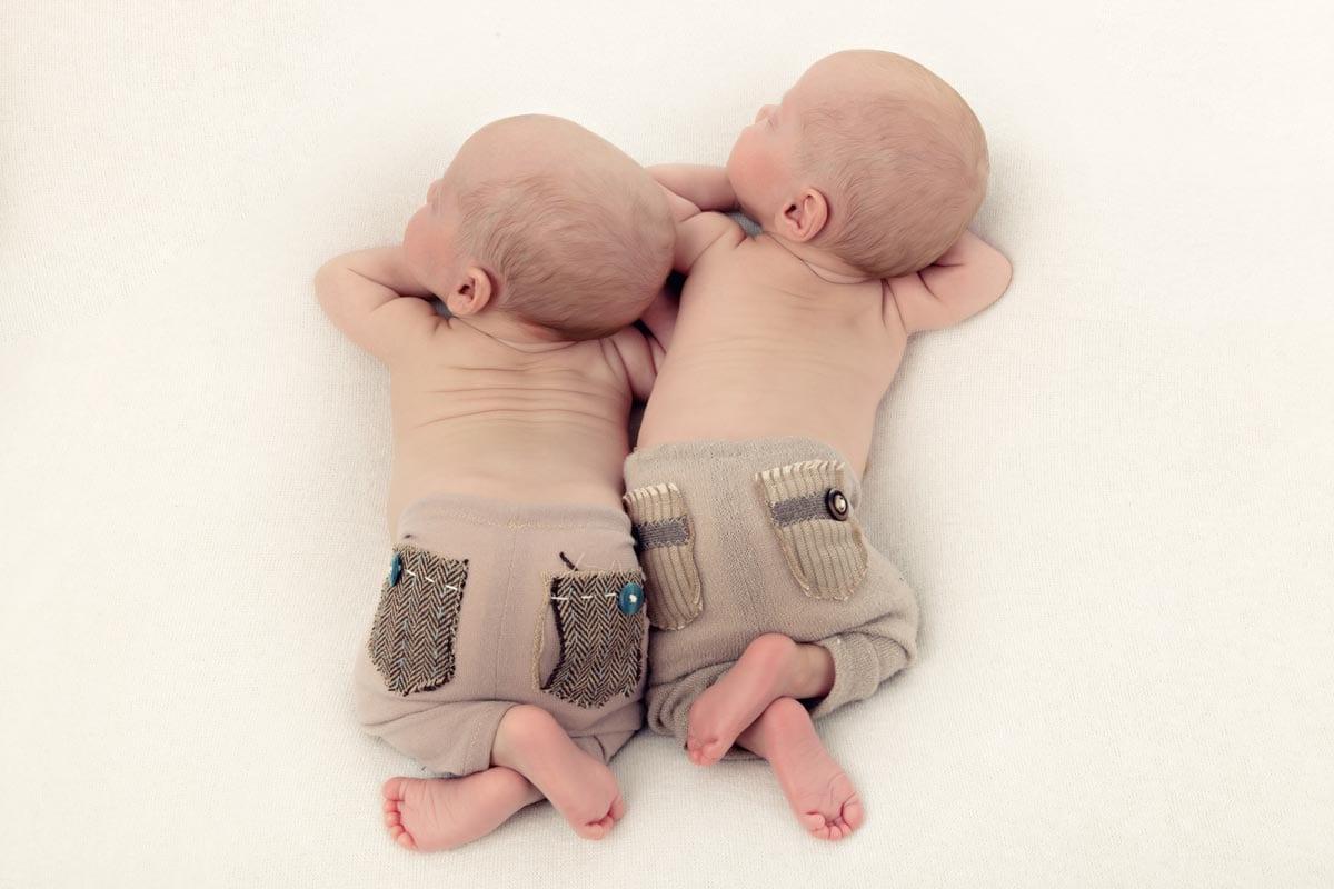 Neugeborene Zwillinge schlafen nebeneinander waehrend des Neugeborenen Fotoshootings im Carmen Bergmann Studio in der Rosenheimer Strasse in Muenchen