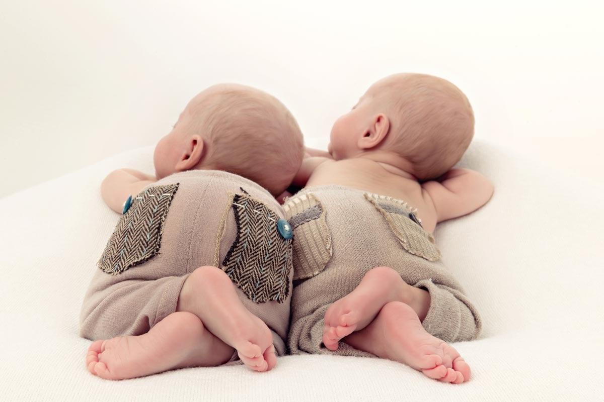 Neugeborene Zwillinge schlafen zusammen mit den Fuessen zur Fotokamera waehrend des Neugeborenen-Fotoshootings im Carmen Bergmann Studio in der Rosenheimer Strasse in Muenchen