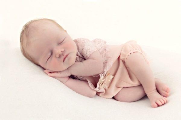 Neugeborenes Maedchen im rosa Kleid schlaeft waehrend des Neugeborenen Fotoshootings im Carmen Bergmann Studio in der Rosenheimer Strasse in Muenchen