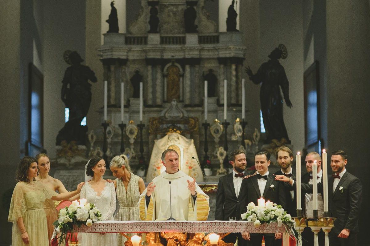 Rares Ion Hochzeitsfotograf fuer Workshop im Carmen Bergmann Studio Muenchen, Braut und Braeutigam an den Seiten eines Priesters in einer Kirche