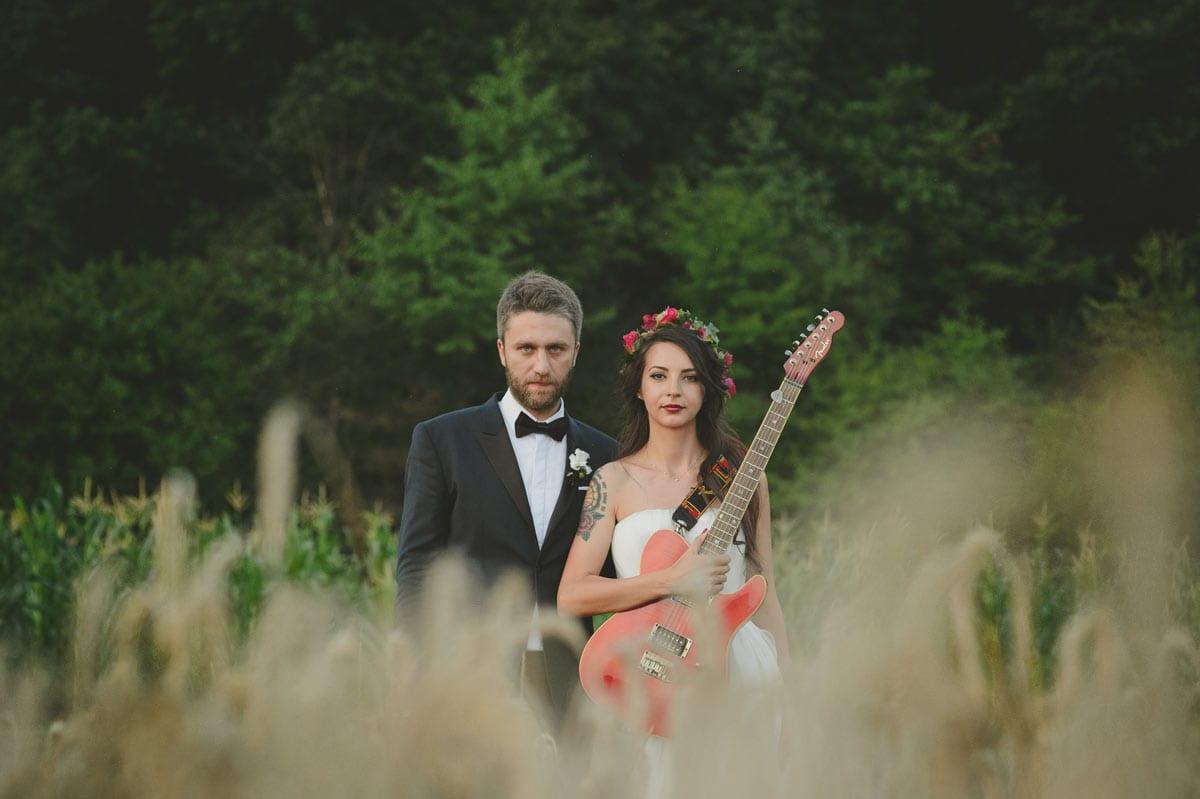 Rares Ion Hochzeitsfotograf fuer Workshop im Carmen Bergmann Studio Muenchen Braut und Braeutigam mit einer Gitarre auf einer Wiese