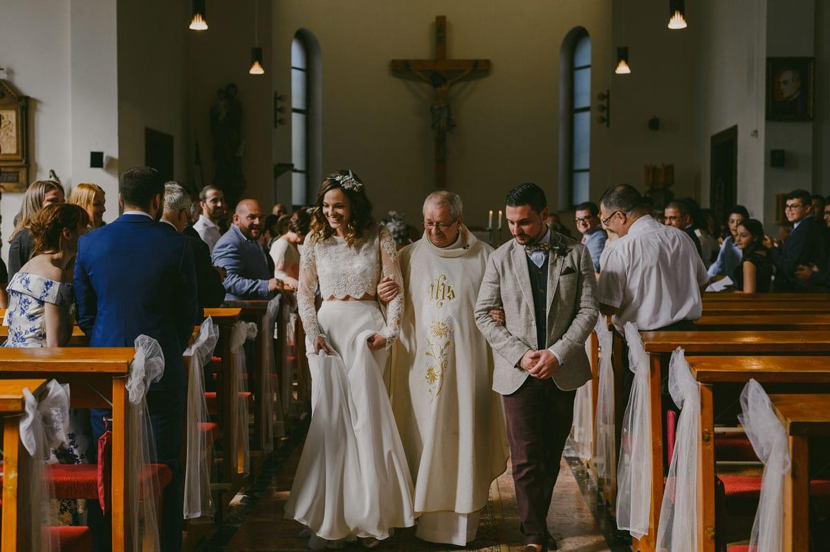 Rares Ion Hochzeitsfotograf fuer Workshop im Carmen Bergmann Studio Muenchen Braut und Braeutigam spazieren mit dem Priester in der Kirche