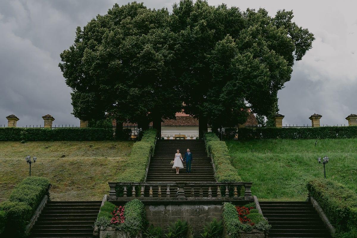 Rares Ion Hochzeitsfotograf fuer Workshop im Carmen Bergmann Studio Muenchen Braut und Braeutigam steigen eine Treppe auf einem Huegel hinab