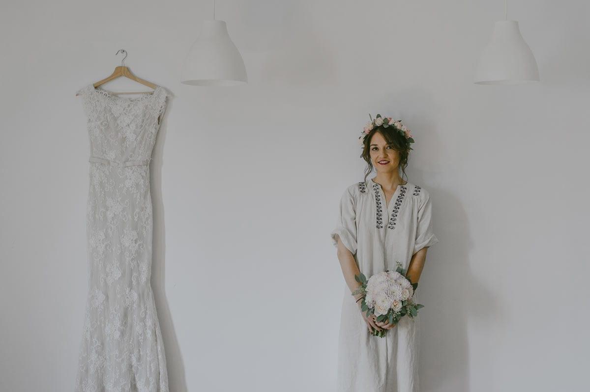 Rares Ion Hochzeitsfotograf fuer Workshop in Carmen Bergmann Studio Muenchen Braut mit weissen Blumen steht in der Naehe des Brautkleides