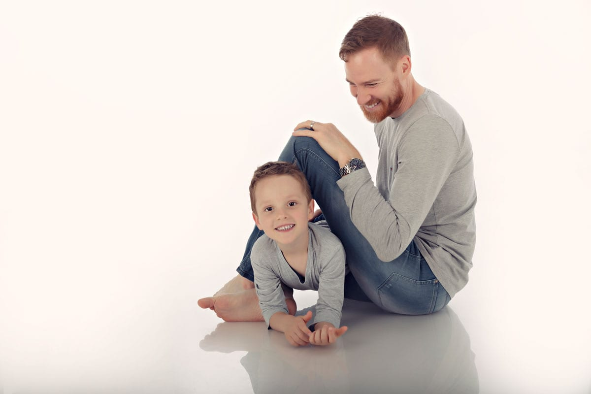 Vater und Sohn sitzen waehrend Familien Fotoshooting in Bergmann Fotostudio