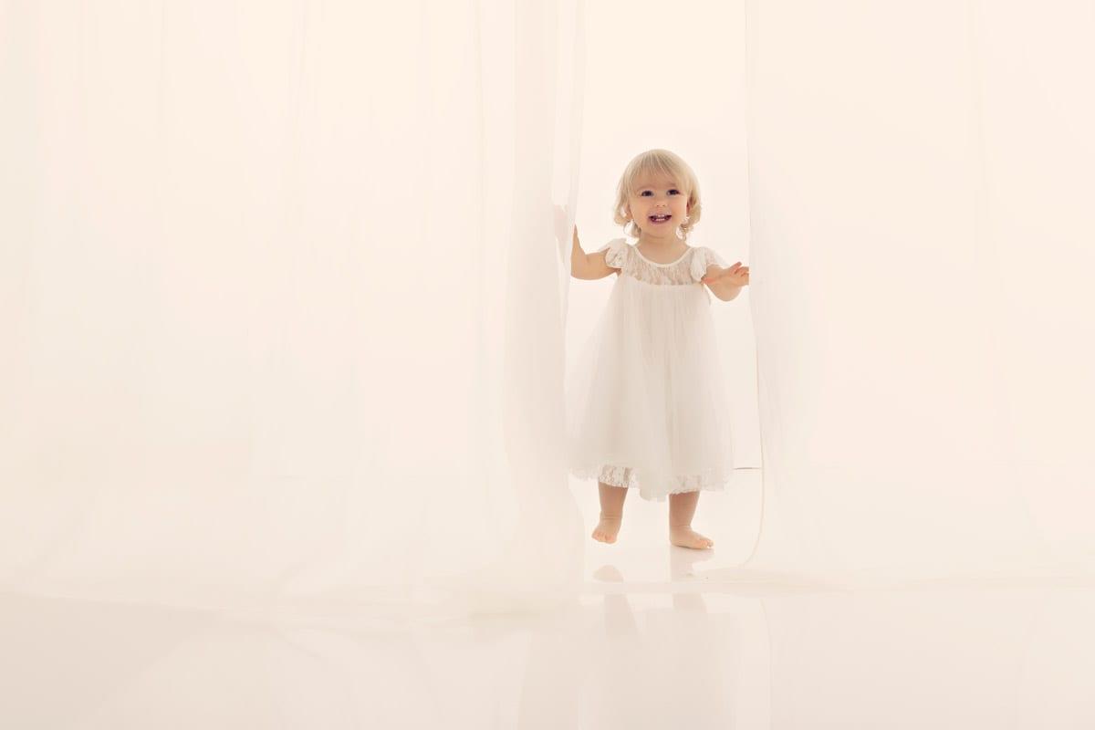 Baby Fotoshooting Muenchen mit Kleinem Maedchen im weissen Kleid waehrend Babyshooting Muenchen