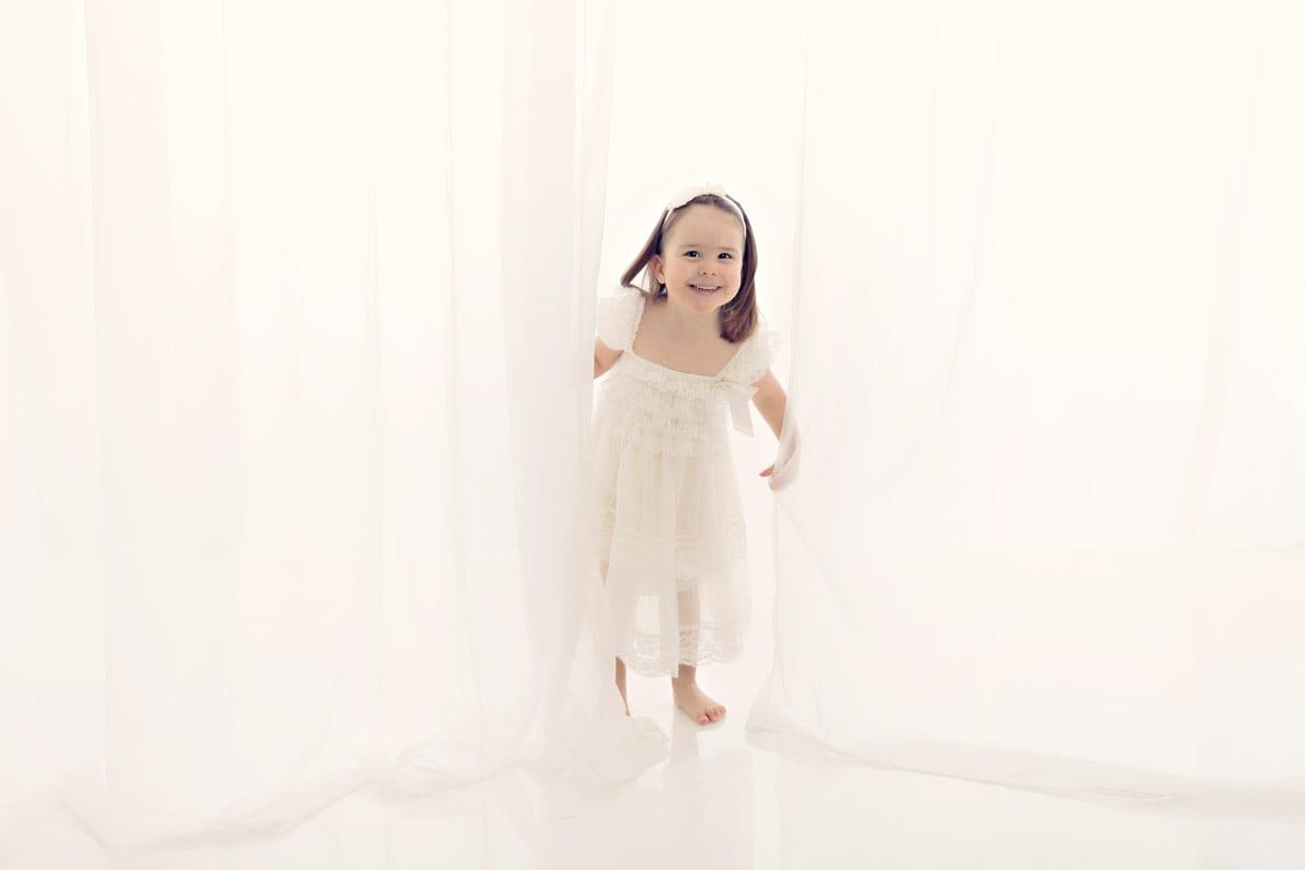 Babyfotografie Muenchen in Carmen Bergmann Studio Baby Fotoshooting mit Kleines Maedchen im weissen Kleid