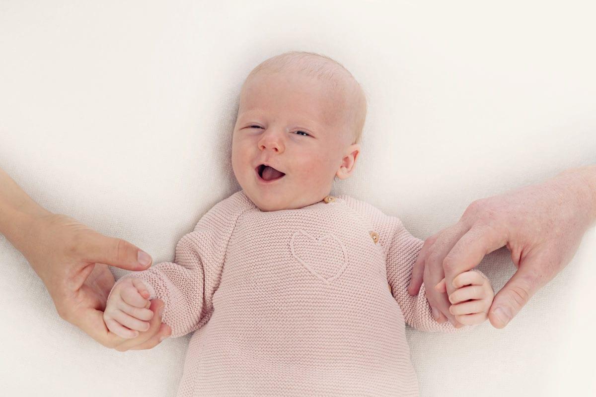 Carmen Bergmann Babyfotografie Muenchen Kleines Baby in der rosafarbenen Bluse waehrend ein Baby Fotoshooting